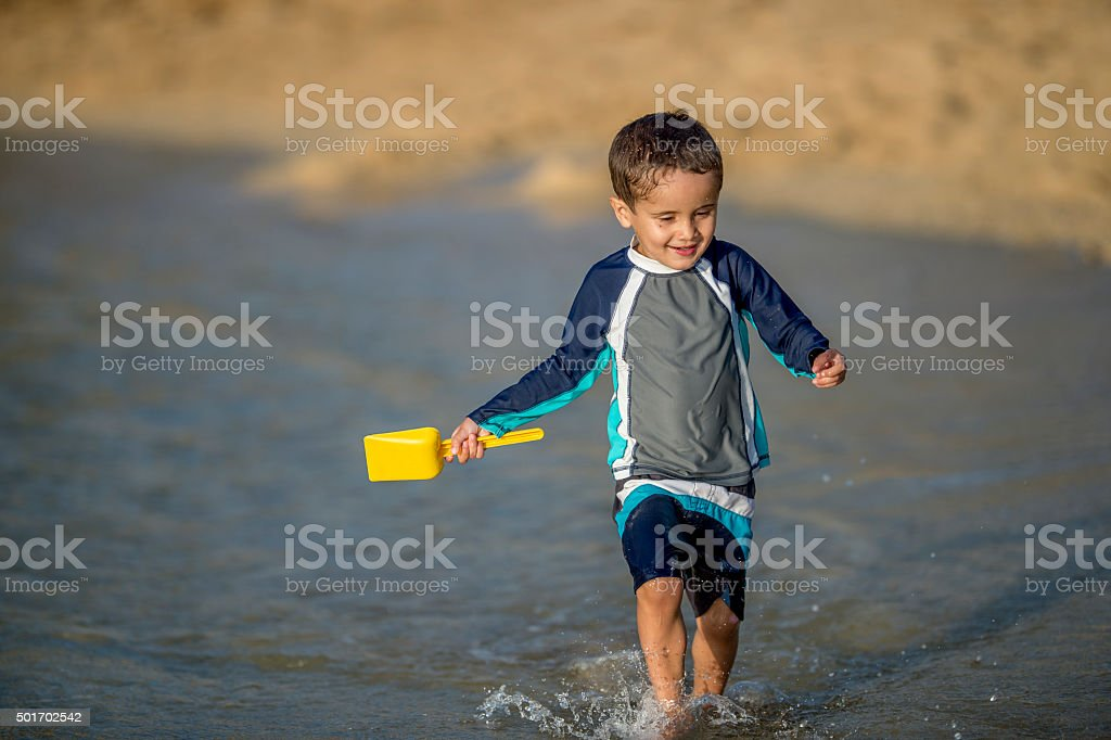 Little Boy Playing in the Surf stock photo