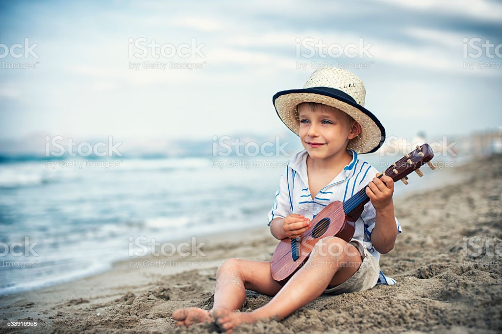 Little boy playing little guitar on the beach. stock photo