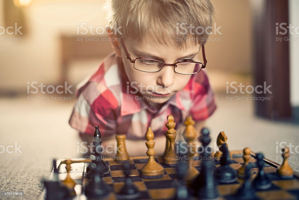 Little boy playing old chess stock photo
