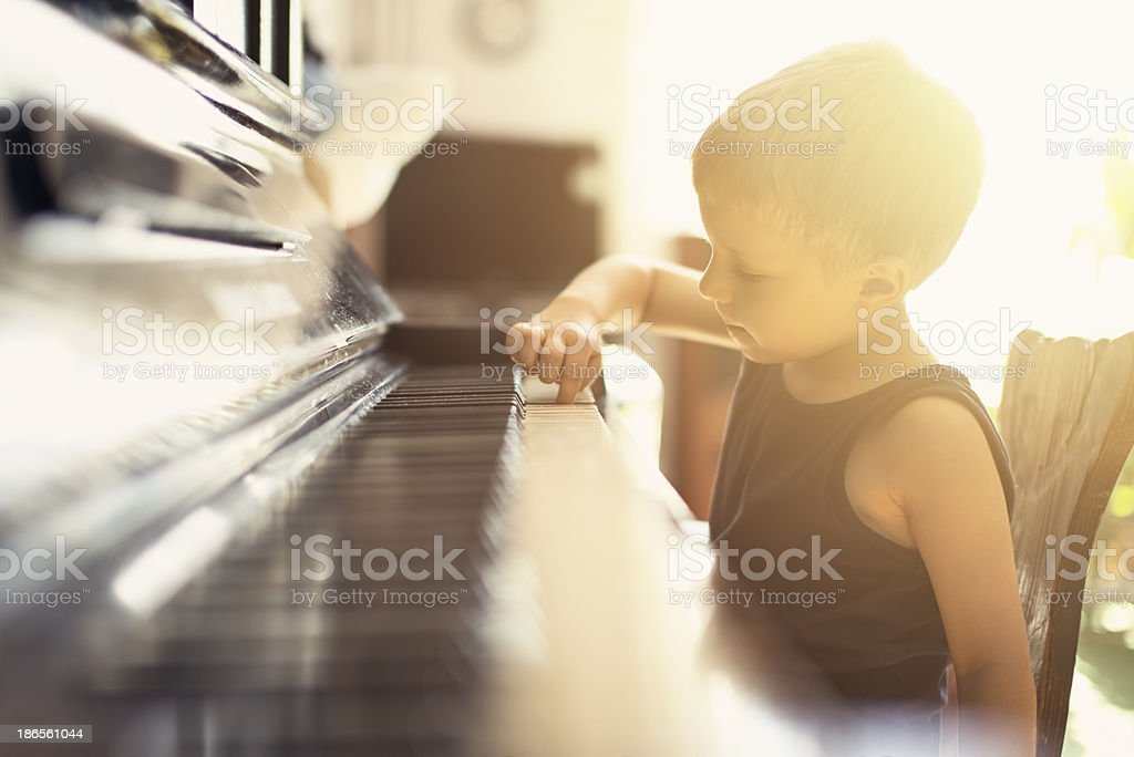 Little boy playing on grandmother piano stock photo