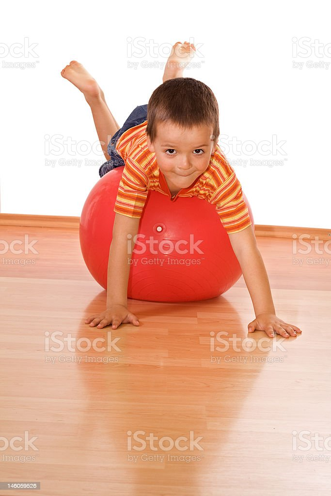 Little boy playing on large red gymnastic ball stock photo