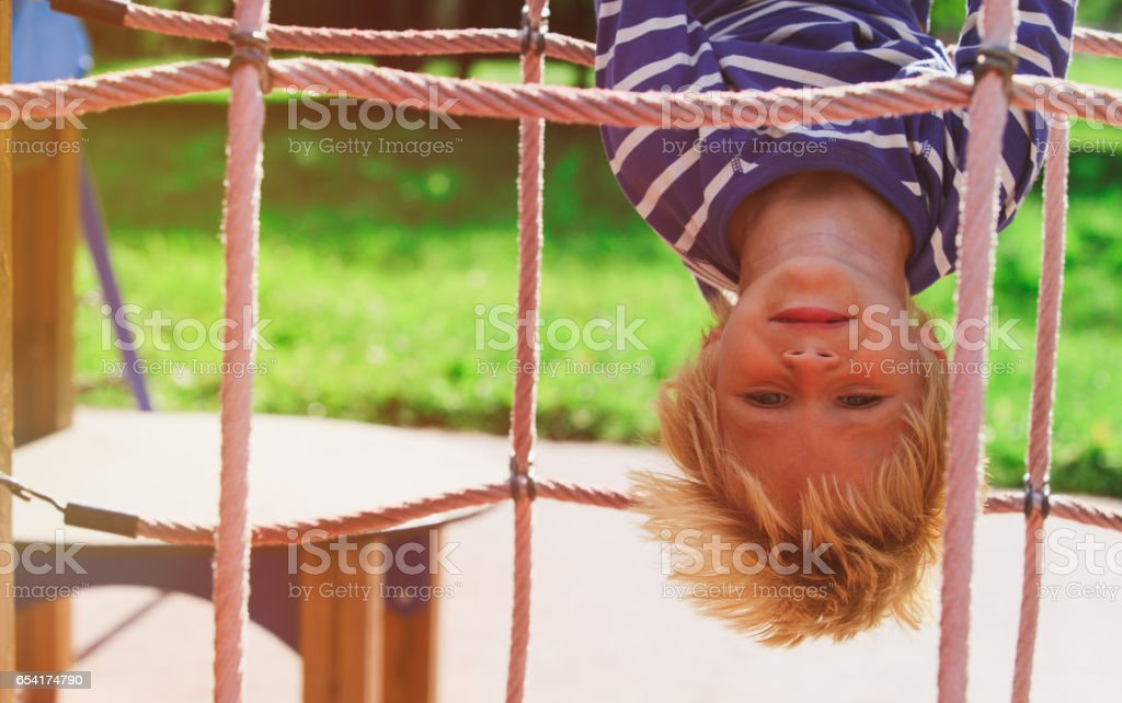 little boy playing on monkey bars at playground stock photo