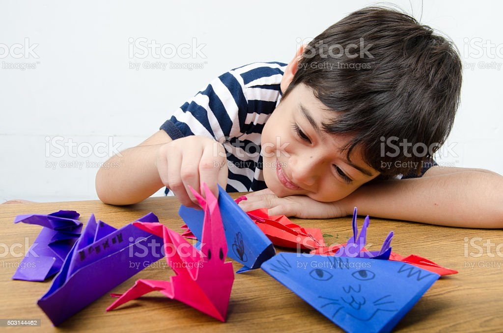 Little boy playing on paper art origami stock photo