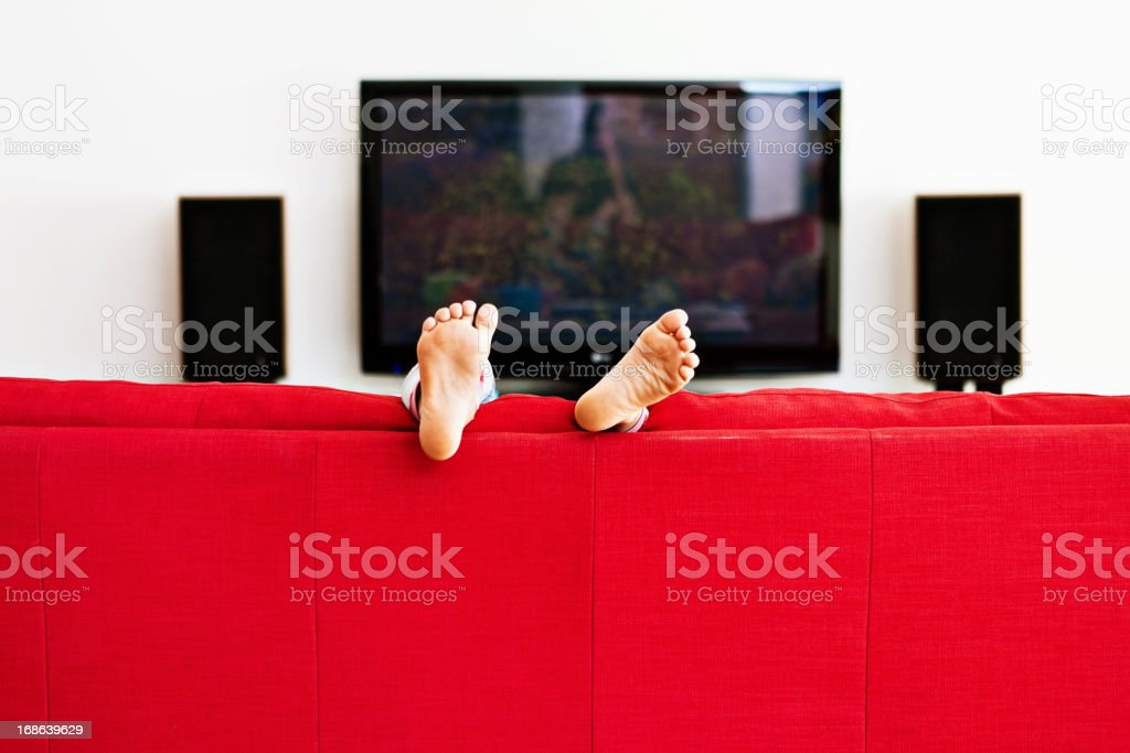 Little boy playing on red couch only his feet visible stock photo