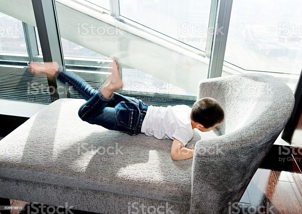 Little boy playing on sofa stock photo