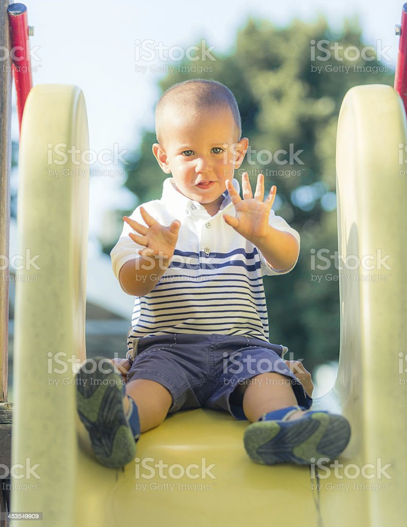 Little Boy Playing on the Slide at Park stock photo
