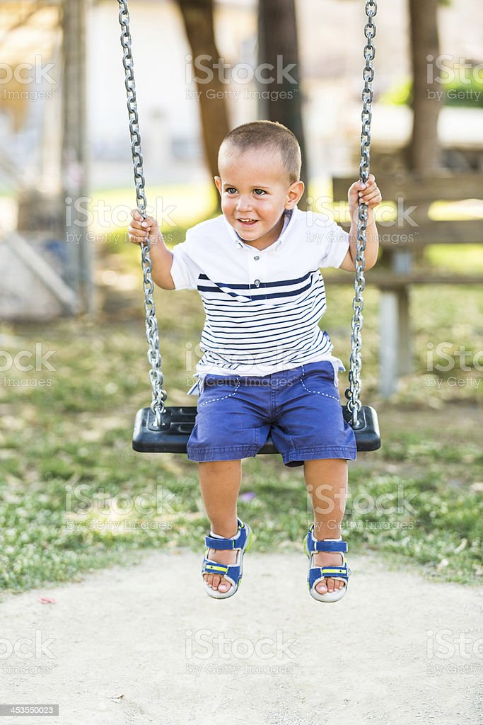 Little Boy Playing on the Swing stock photo