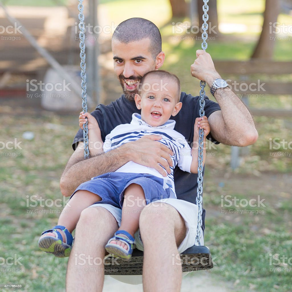 Little Boy Playing on the Swing with Father or Uncle stock photo