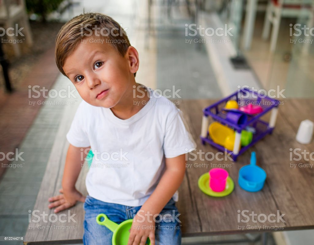 Little Boy Playing on The Table in The Cafe stock photo