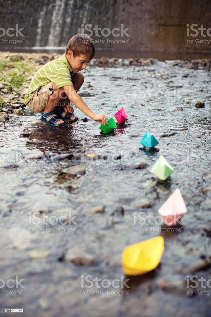 Little boy playing paper boats in stream stock photo