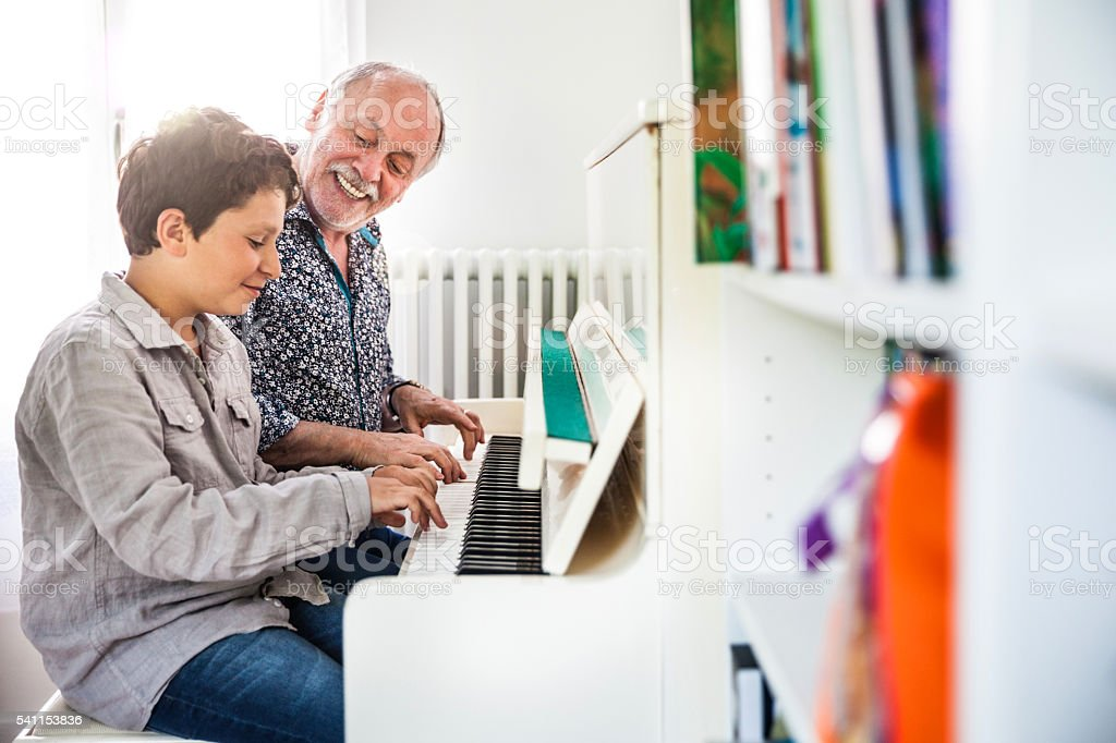 Little boy playing piano with his grandfather stock photo