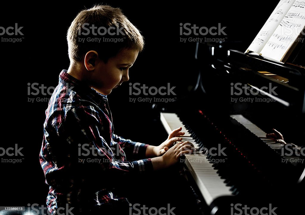 Little boy playing piano with sheet music stock photo