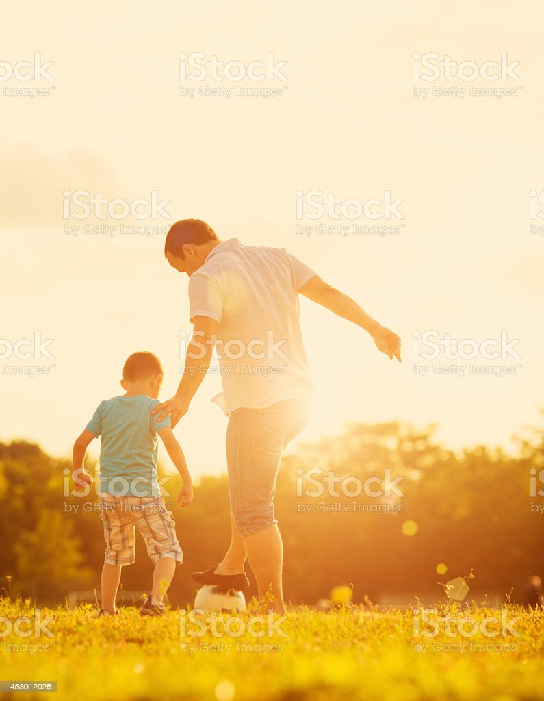 Little Boy Playing Soccer With Father Outdoors. stock photo