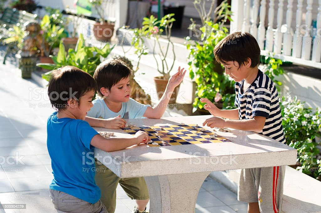 Little boy playing stone chess together royalty-free stock photo