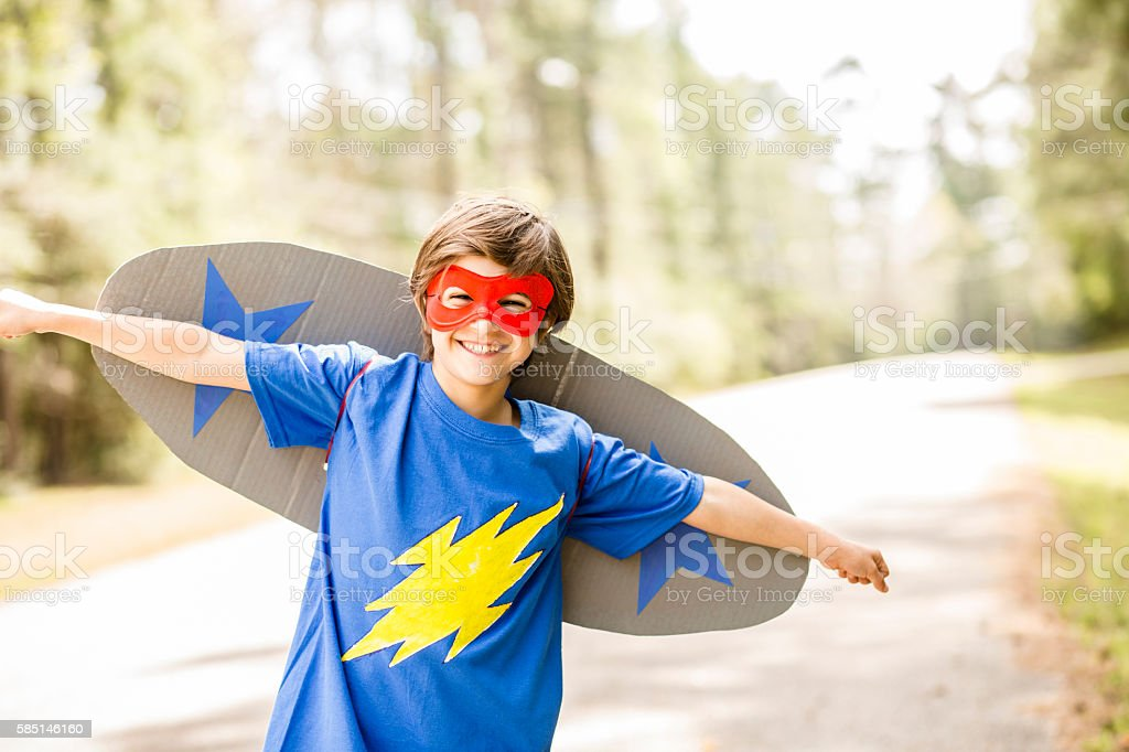 Little boy playing superhero outdoors. stock photo