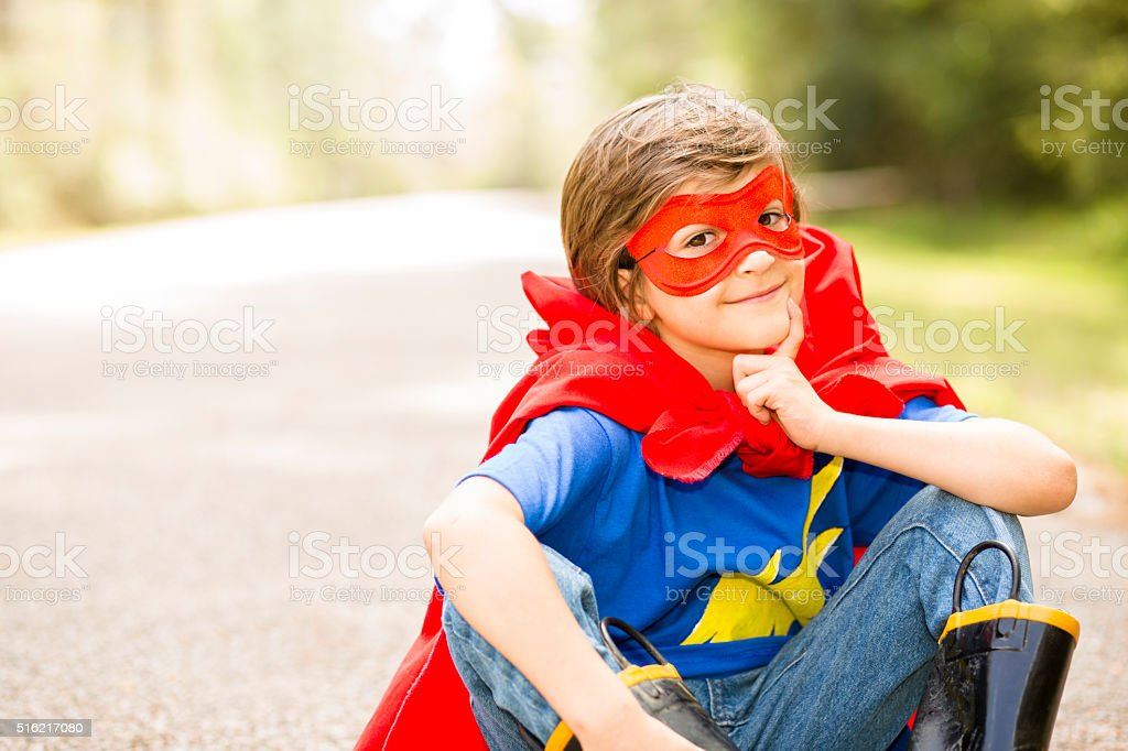 Little boy playing superhero outdoors. Pretend, dress up. stock photo