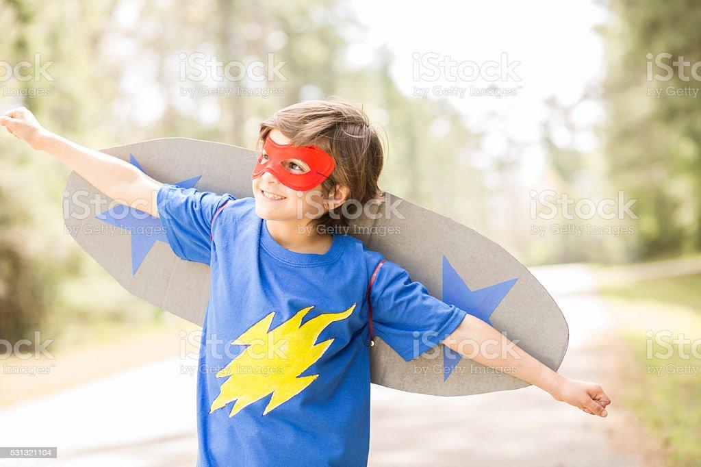 Little boy playing superhero outdoors. Pretend, dress up. stock photo