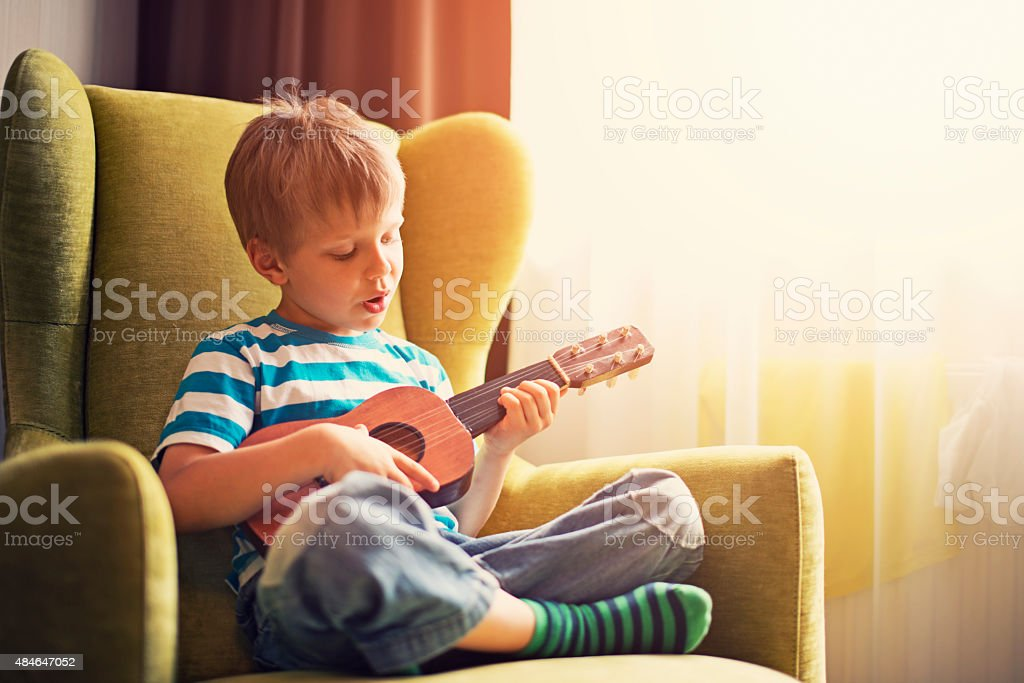 Little boy playing the guitar and singing stock photo