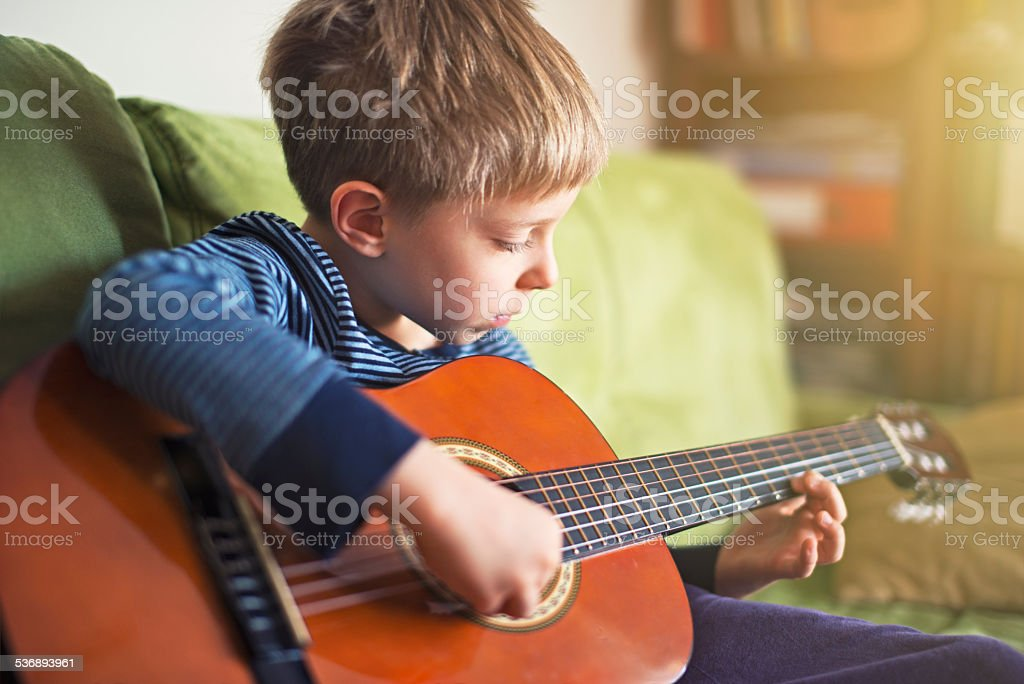 Little boy playing the guitar stock photo