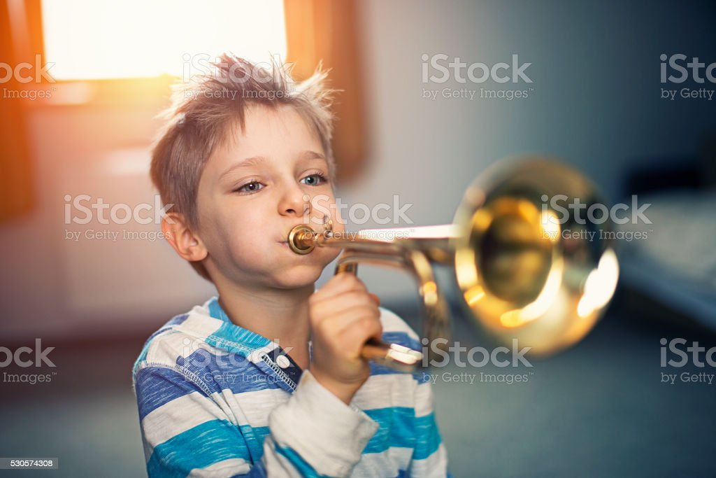 Little boy playing trumpet at home stock photo