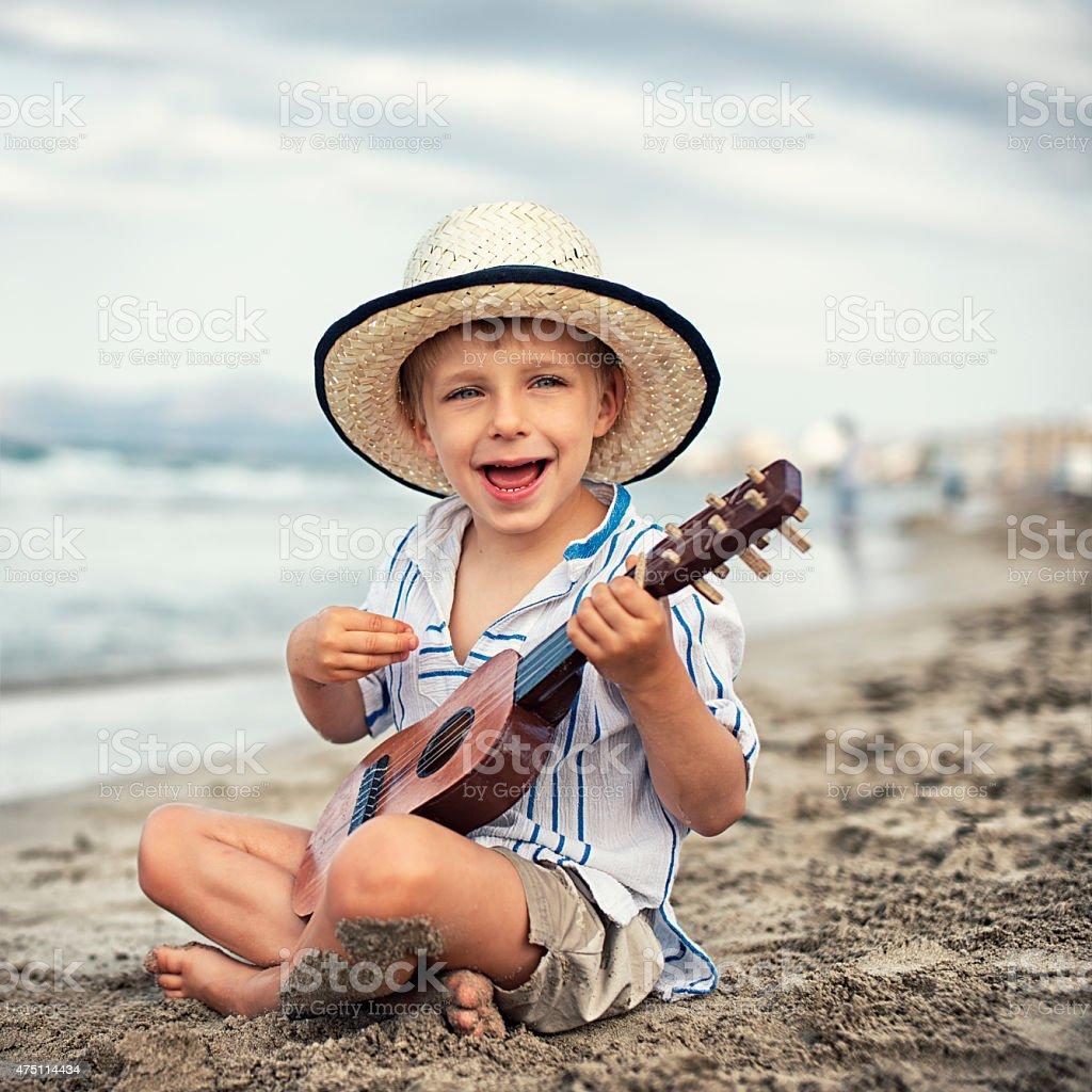 Little boy playing ukulele on the beach. stock photo