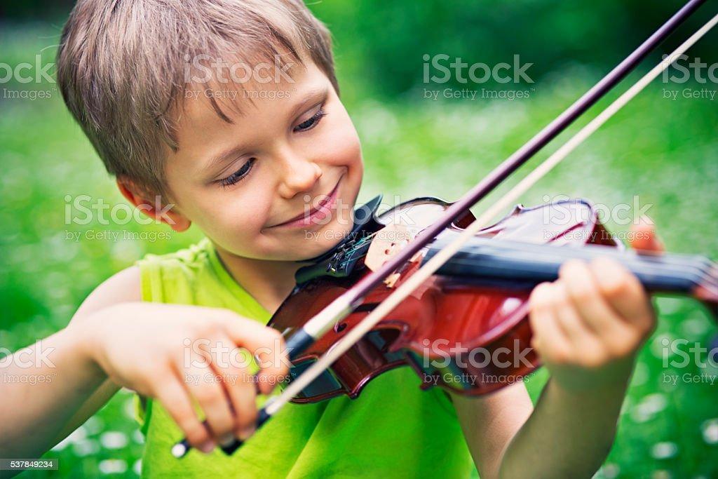 Little boy playing violin on grass field stock photo