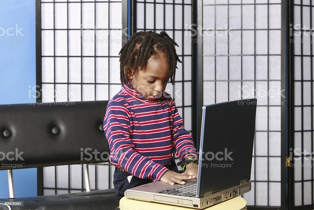 Little boy playing with a computer royalty-free stock photo