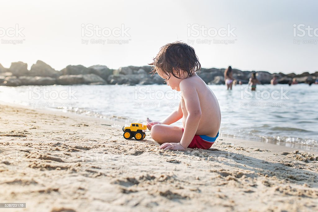 Little boy playing with a toy on the beach. stock photo