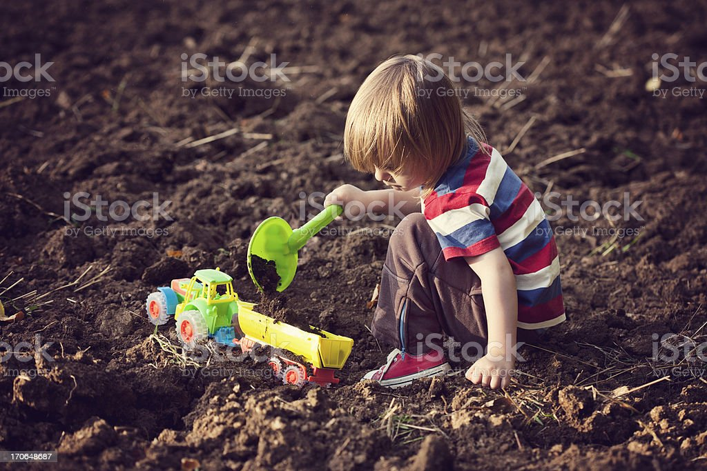 Little boy playing with a toy tractor stock photo