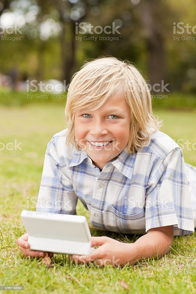 Little boy playing with a video game at the park royalty-free stock photo