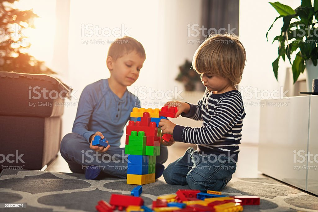 Little boy playing with blocks with little brother stock photo