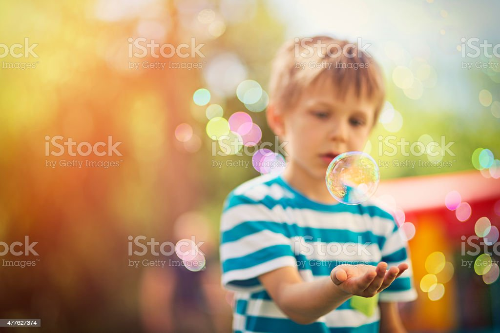 Little boy playing with bubbles at the outdoors kids party stock photo