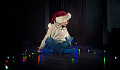 Little boy playing with christmas lights