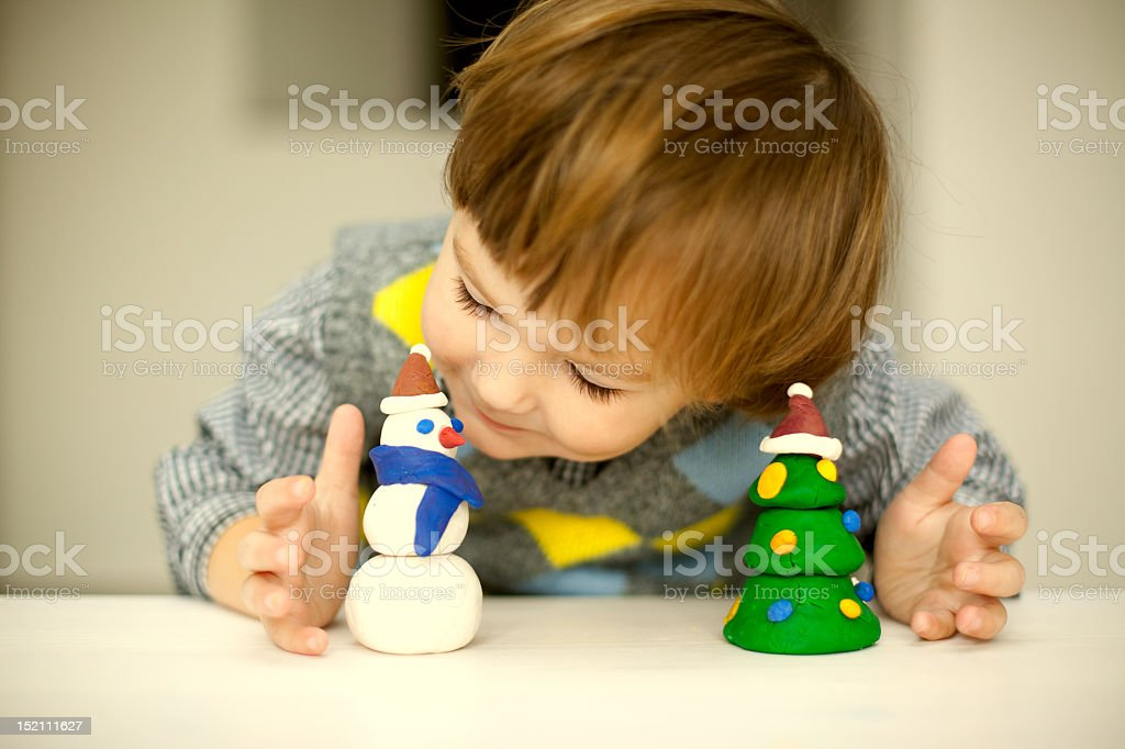 Little boy playing with Christmas themed clay figures stock photo