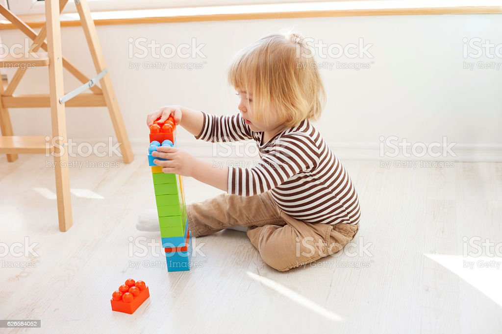 Little boy playing with colorful plastic blocks stock photo