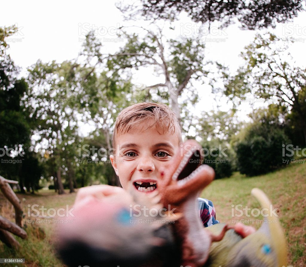 Little boy playing with dinosaur toys in garden stock photo