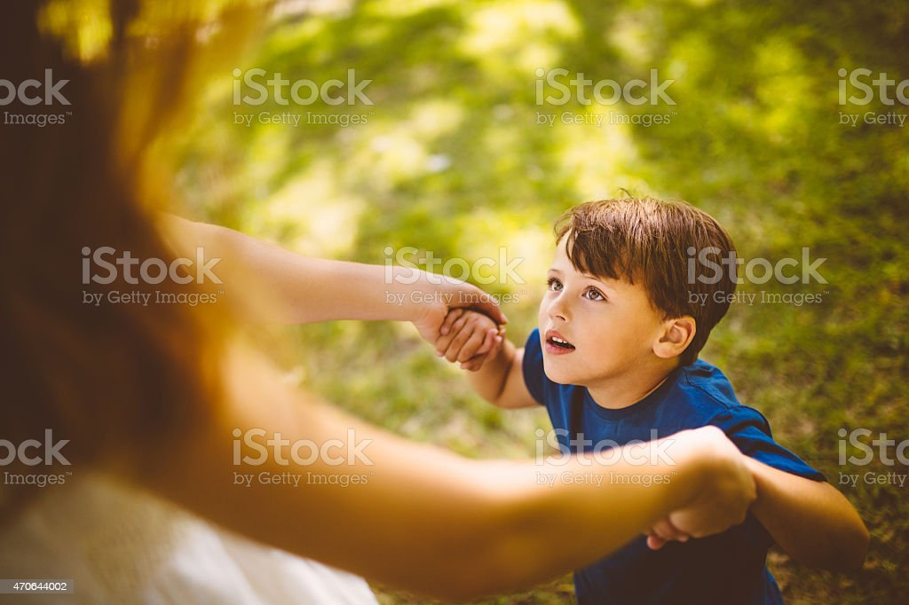 Little boy playing with his mom outside on the grass stock photo