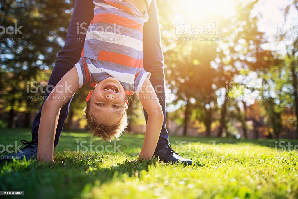 Little boy playing with mother in park stock photo