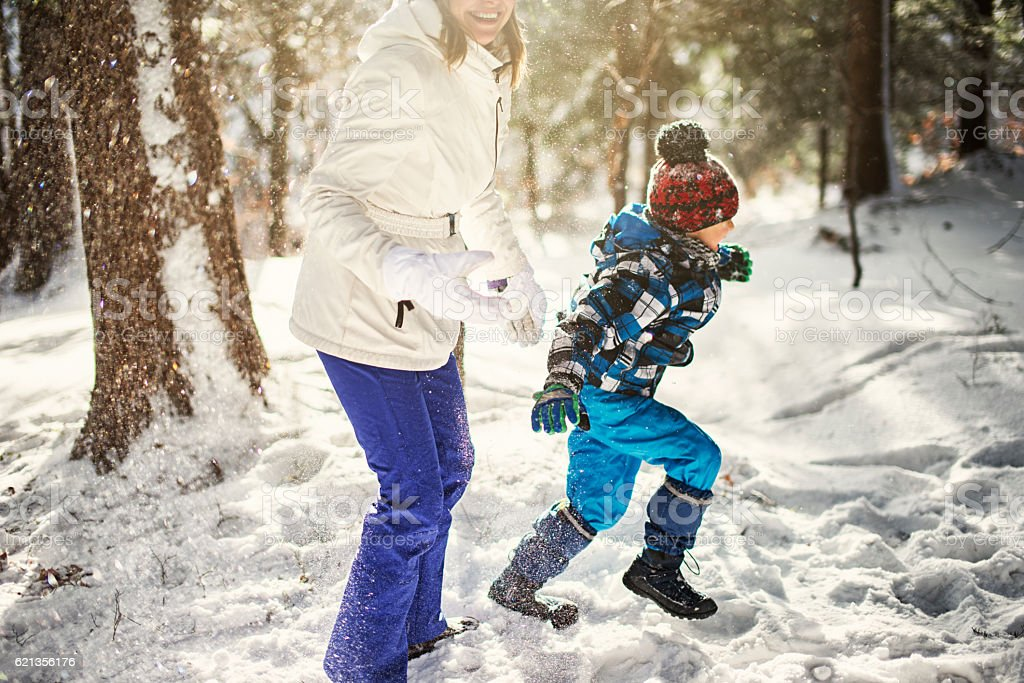 Little boy playing with mother in winter forest stock photo
