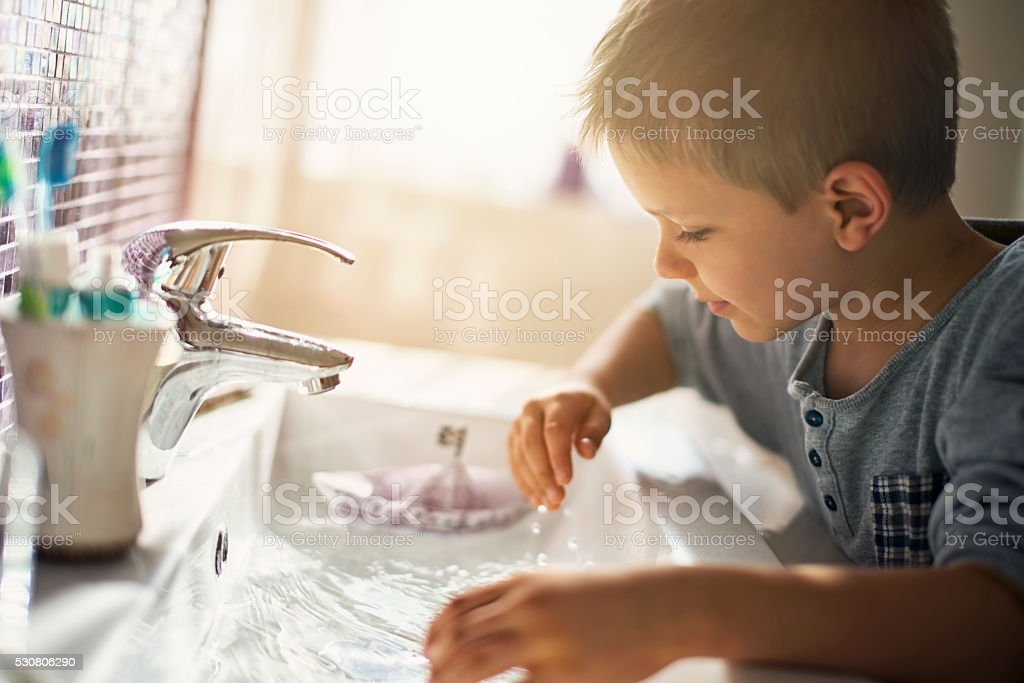 Little boy playing with paper boat in sink stock photo