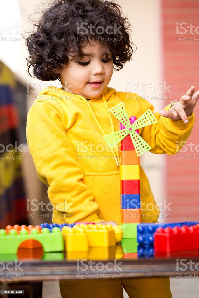 Little boy playing with lego toys stock photo