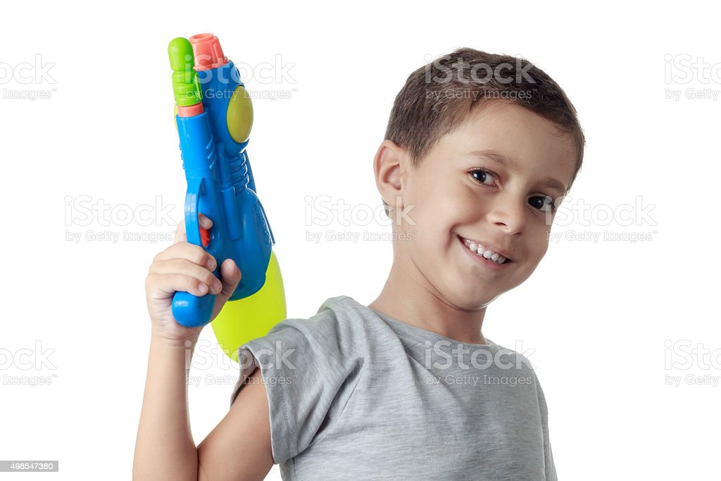 Little boy playing with plastic water gun isolated on white. stock photo