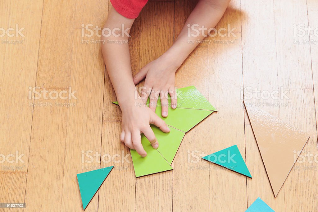 little boy playing with puzzle, early education stock photo
