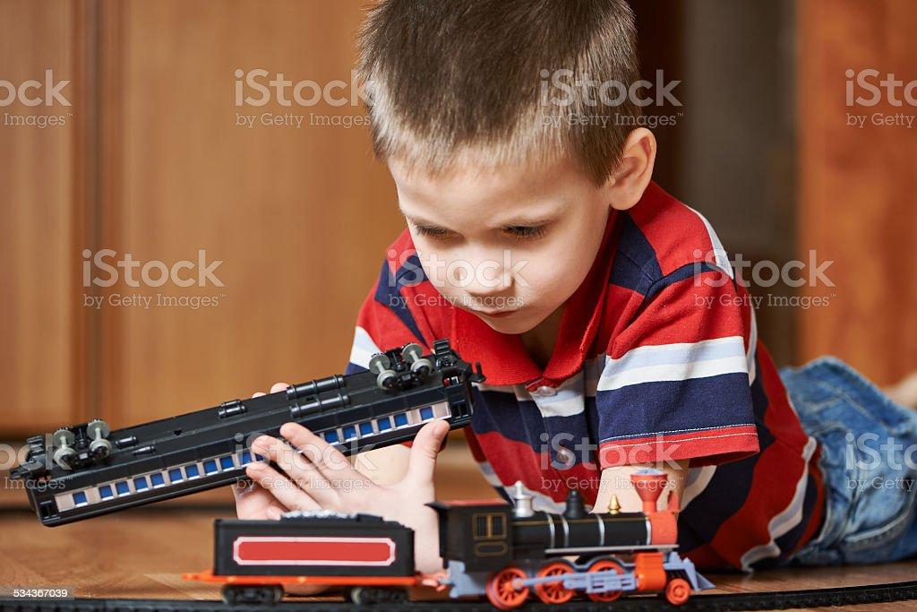 Little boy playing with railway lying on floor stock photo