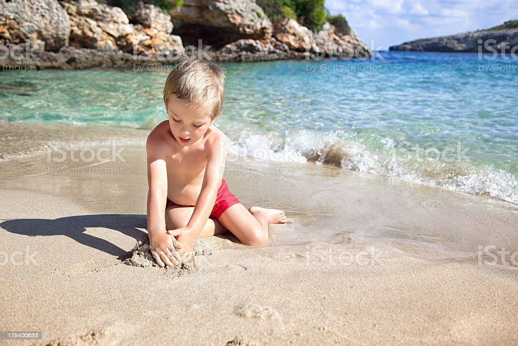 Little Boy Playing With Sand on the Beach royalty-free stock photo