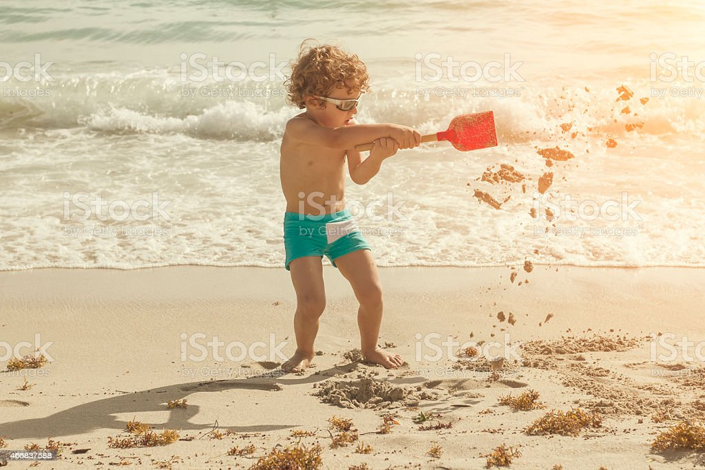 A little boy playing with sand on the beach stock photo