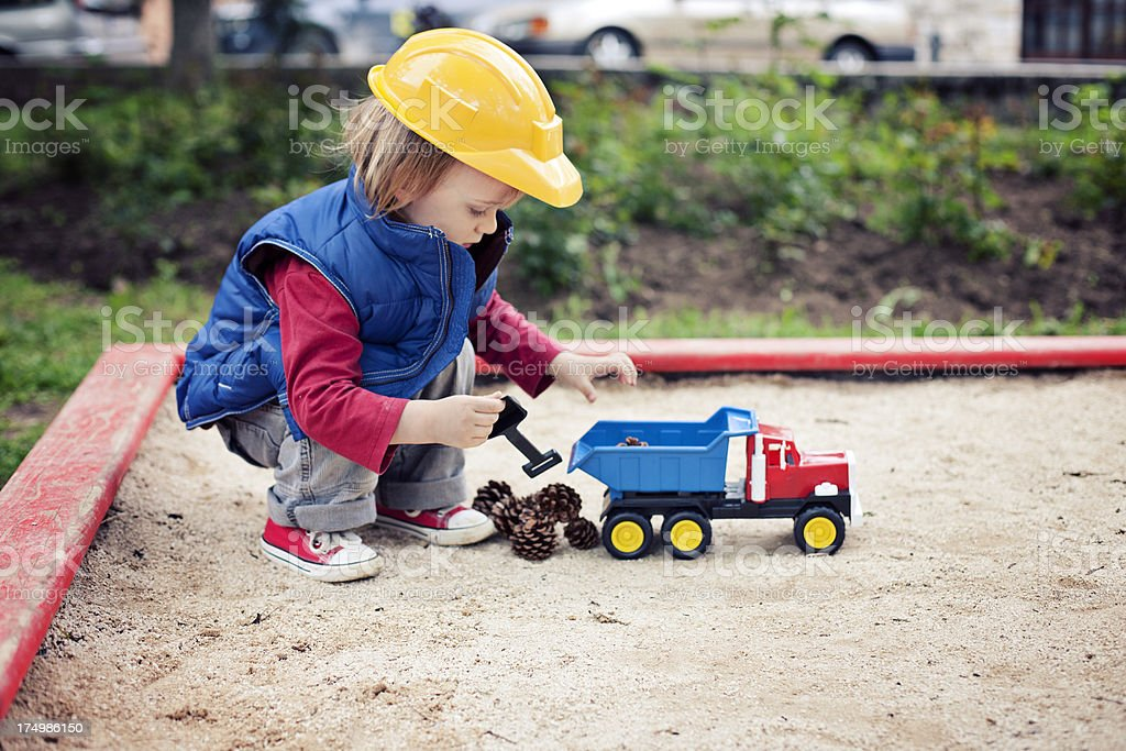 Little boy playing with toy truck in the sandbox stock photo