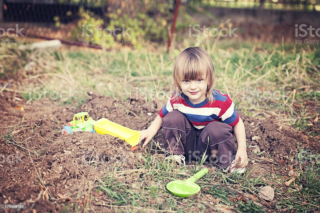 Little boy playing with toys outdoors royalty-free stock photo