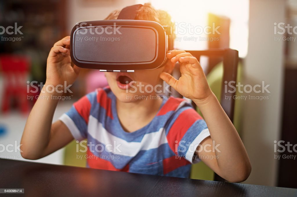 Little boy playing with virtual reality headset stock photo