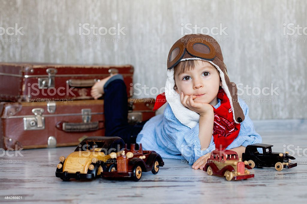 Little boy, playing with wooden cars, indoor, suitcases behind him stock photo